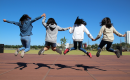 girls holding hands and jumping