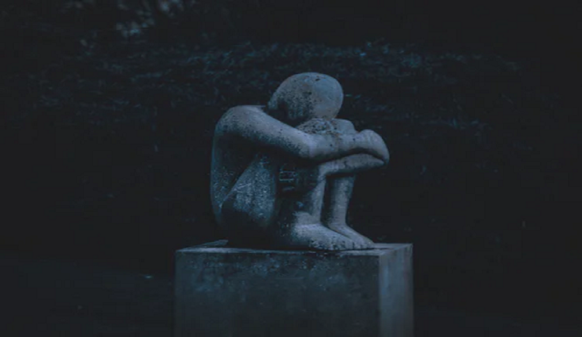 sad sculpture sitting alone with heads down and knees bent