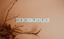 Dry leaves and alphabet blocks spelling meditate